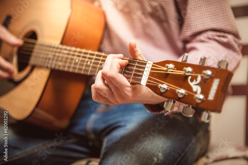 Closeup portrait of man playing on acoustic guitar on sunny day