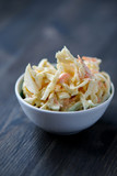 Coleslaw in a bowl on a wooden table