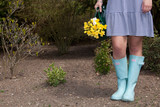 Woman in gumboots carrying yellow daffodils