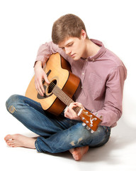 man sitting on floor and playing on classic guitar