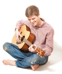smiling man sitting on floor and playing on acoustic guitar