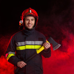 Smiling firefighter holding axe.