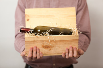 Closeup shot of man in shirt showing wine in wooden box