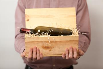 Closeup shot of man in shirt showing wine in wooden box