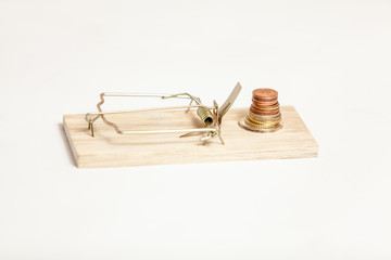 Closeup shot of mouse trap with pile of coins as bait