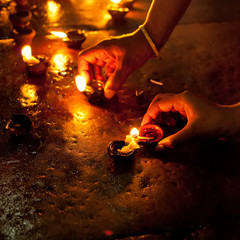 People burning oil lamps in Hindu temple. India