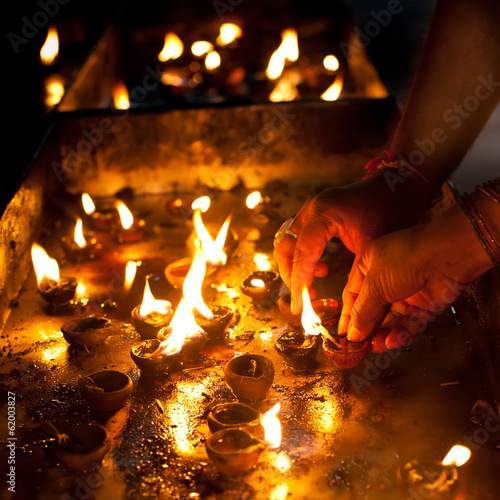People burning oil lampsl in Hindu temple