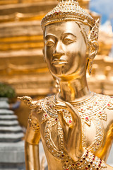 Golden Kinnari statue at Temple of Emerald Buddha. Thailand