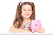 Little girl sitting at table and holding a piggybank
