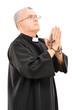 Mature priest holding a wooden cross and praying to god