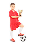 Full length portrait of junior football player holding a trophy