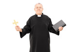Mature reverend in black mantle holding bible and a cross