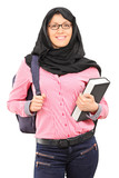 Muslim female student with backpack holding a book