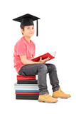 Young boy with mortarboard seated on a stack of books