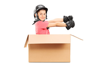 Playful boy with helmet sitting in carton box