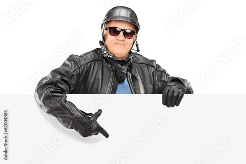 Mature biker pointing on a blank panel