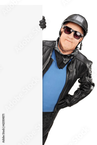 Mature male biker standing behind blank panel