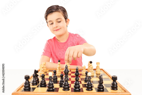 Young boy playing chess seated at a table