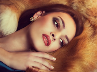 Portrait of beautiful young woman with makeup in fur