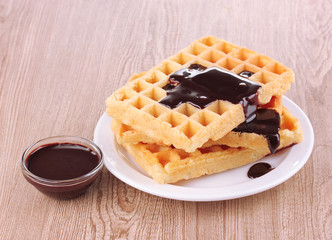 Tasty waffles with chocolate on plate on wooden background