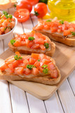 Delicious bruschetta with tomatoes on cutting board close-up