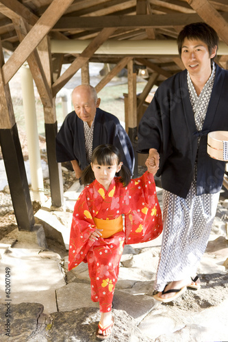 family in yukata going up stone steps