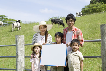 family standing in front of fence of stock farm