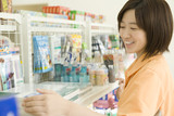 salesclerk of convenience store tidying up goods poster
