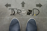 Hand drawn TREND  design word on front of business man feet as c