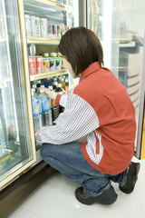 salesclerk of convenience store tidying up drink
