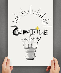 hannd show  light bulb and CREATIVE word design on paper backgro