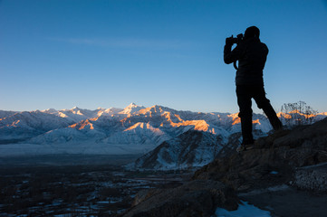 Silhouette of traveler taking photo of sunrise over mountain.