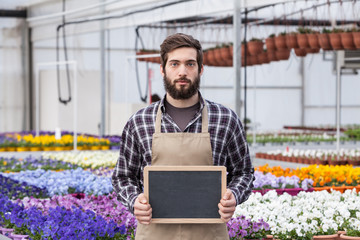 Male Garden Worker Holding an blank chalkboard in a greenhouse