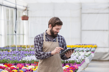 Young adult male garden worker using digital tablet