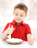 Cute little boy is eating cottage cheese