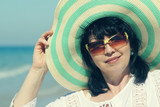 Portrait elegant middle aged woman with hat sunny day at beach