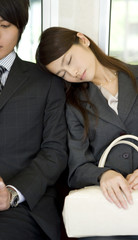 business woman having a nap while sitting on seat of train