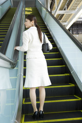 rear view of business woman using the escalator