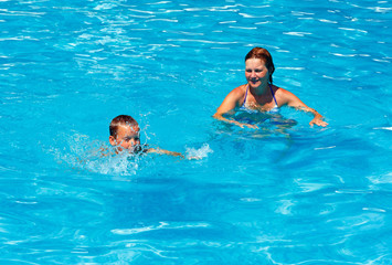 Mother train her son to swim in the pool.