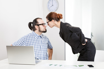 Angry businesswoman is slapping across the businessman's face.