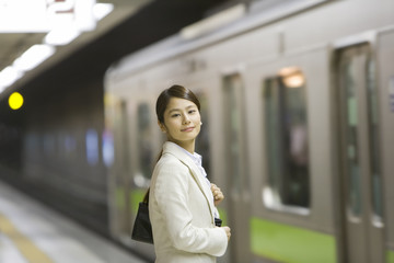 business woman standing on platform and is looking at the camera