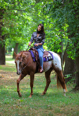 Young beautiful cowgirl with horse in forest