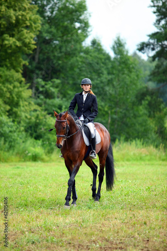 Elegant young woman riding horse