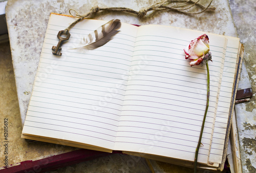 Blank sheet in an old notebook framed with key, feather and dead