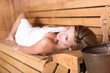 Lady relaxing in traditional wooden sauna.