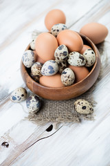 Chicken and quail eggs in a wooden bowl, vertical shot