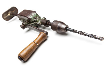 Old rusty hand drill over white