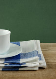 White coffee cup and dishcloth on old wooden table over green ba
