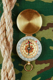 Compass and rope on a camouflage background