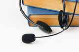 Headphones with a microphone and a stack of books on white backg